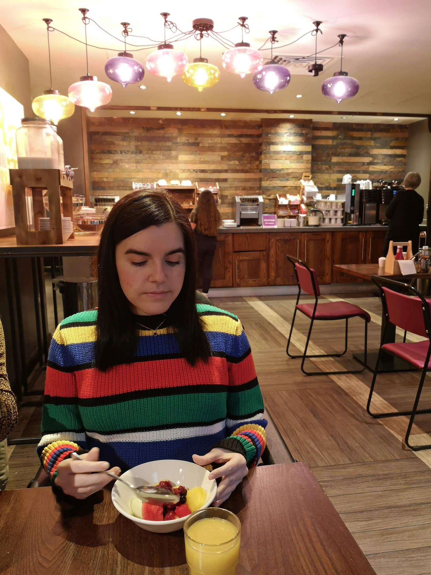 Emma eating breakfast at her Premier Inn hotel. Emma is wearing a multicoloured stripe jumper.