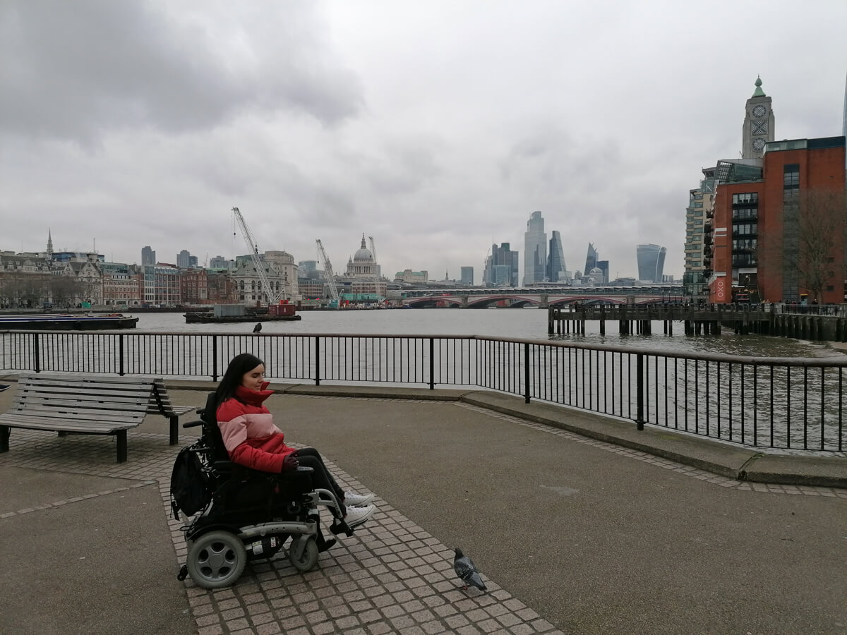 Emma talking to a pigeon in South Bank. The London skyline and OXO tower is in the background.