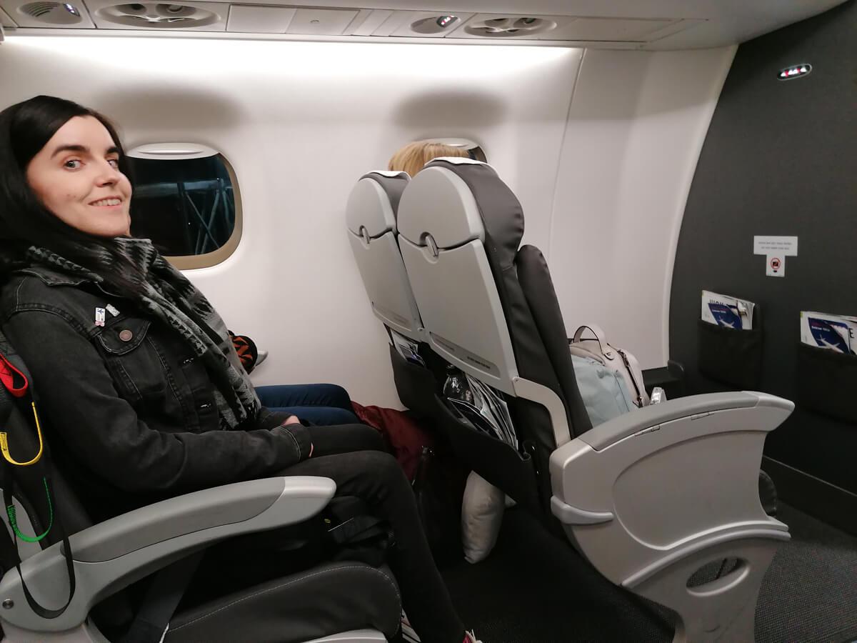 Emma sitting in business seat on British Airways flight.