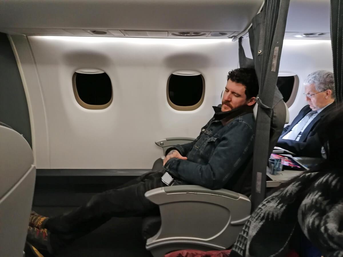 Allan sitting with his eyes shut sitting in business seat on British Airways flight.