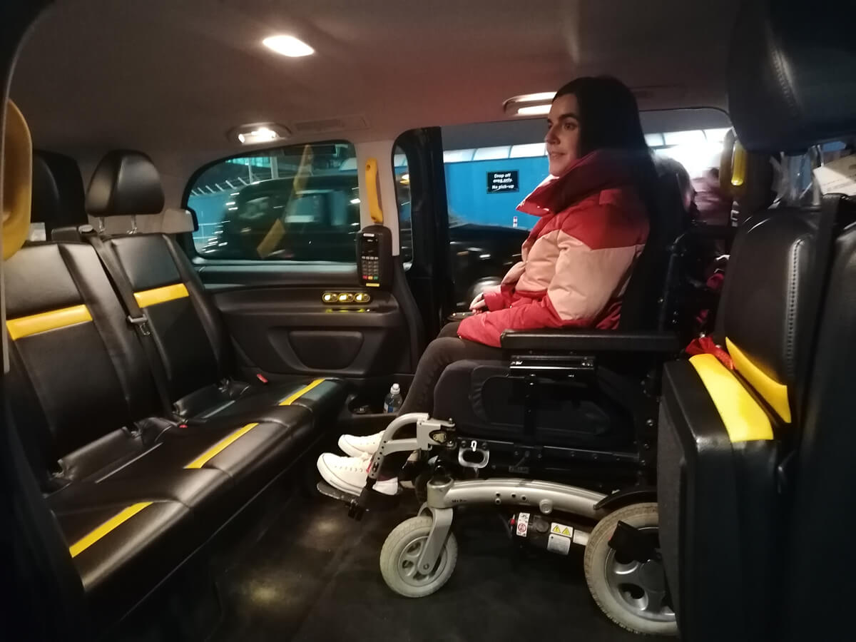 London sitting in her wheelchair inside the wheelchair accessible taxi.