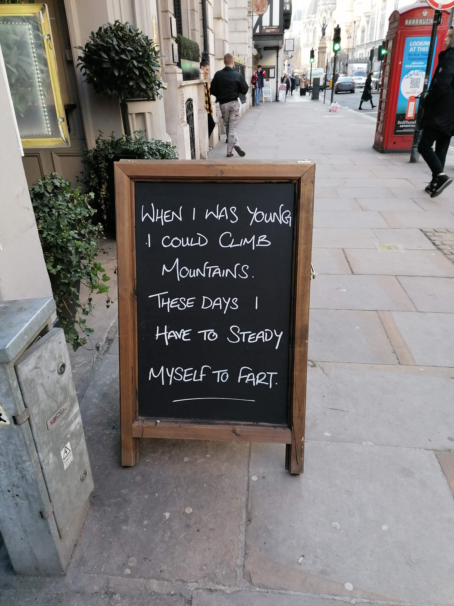 """A chalk board outside a pub with """"When i was young I could climb mountains, these days I need to steady myself to fart""""."""
