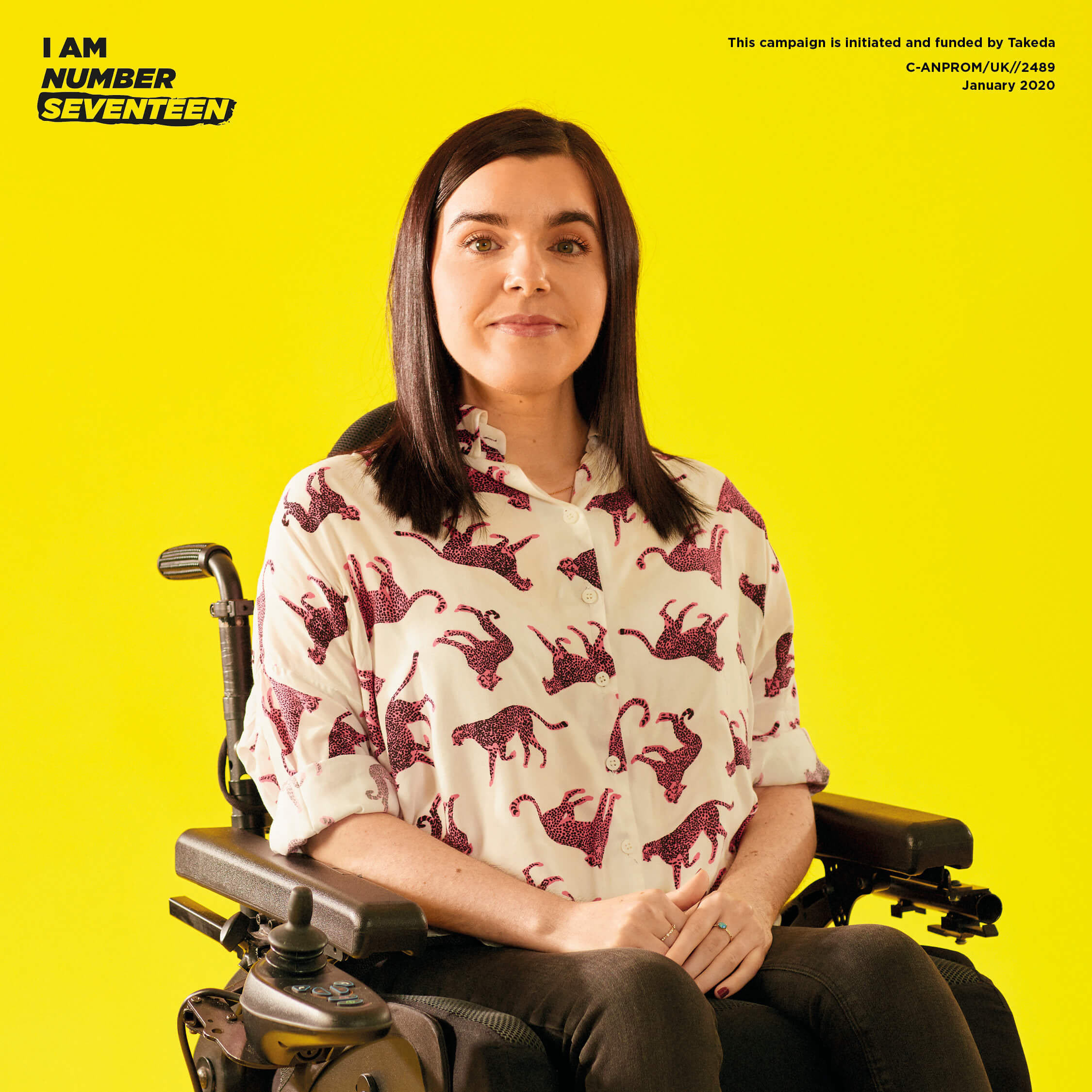 Emma sitting in her wheelchair against a yellow background. Emma is wearing black skinny jeans and a white shirt with pink leopards.