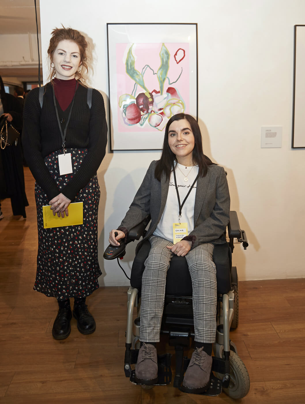Emma sitting in her wheelchair while artist, Rachel Clarke stands beside her. Behind them is the painting Rachel created to represent Emma.