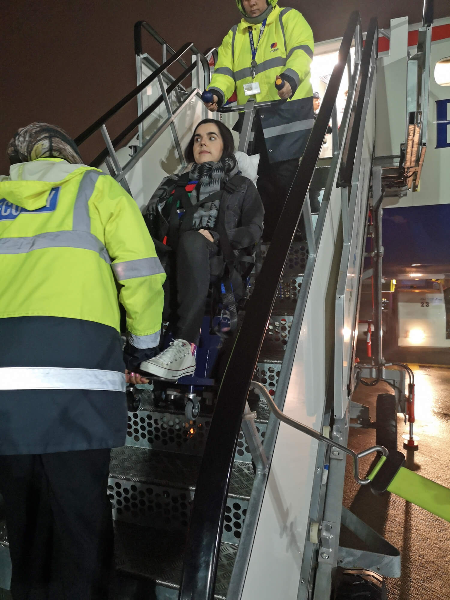Emma sitting in the stairclimber and being taken up the aircraft stairs with airport staff. This is a view from the bottom of the stairs looking up.