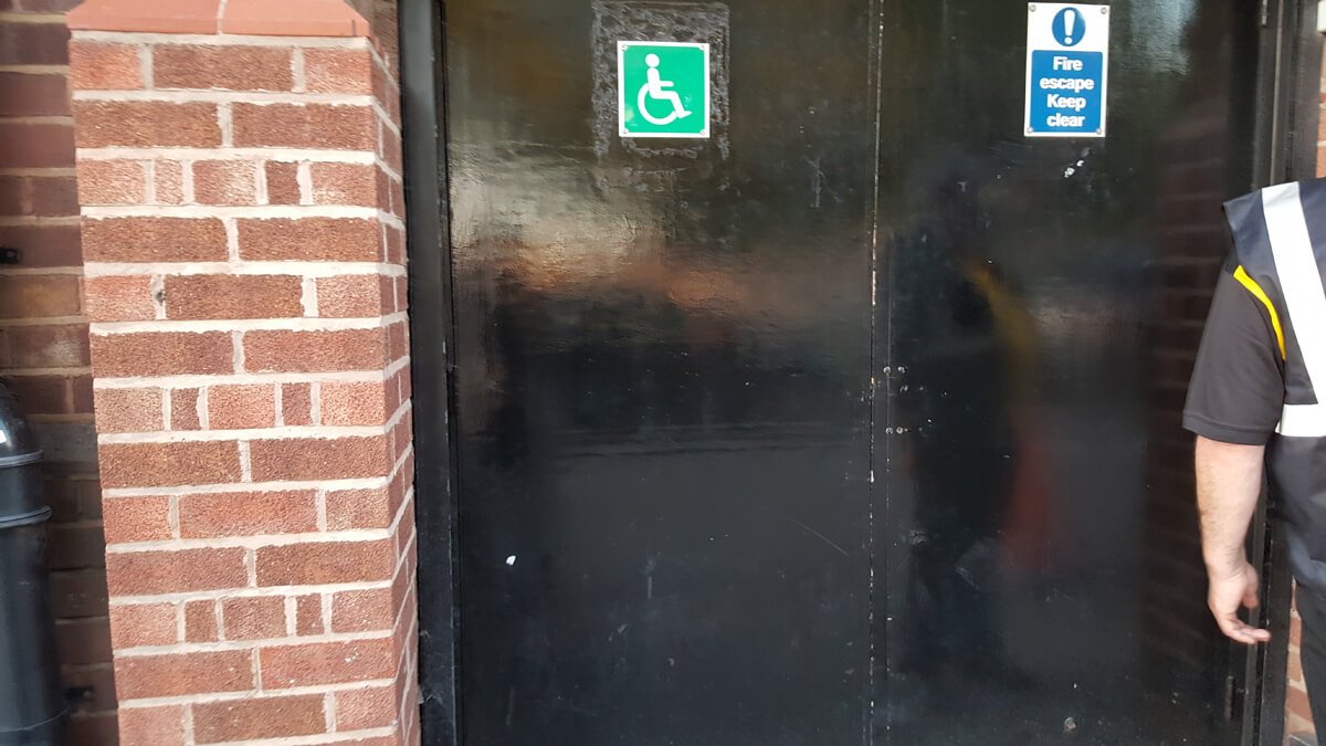 A black door with a green and white wheelchair symbol. This is the wheelchair accessible entrance to the O2 Apollo Manchester.