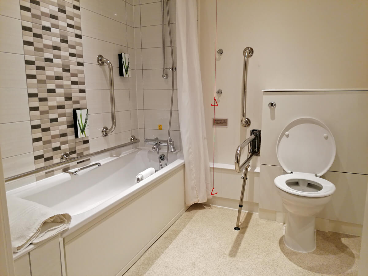 The toilet and bath in the accessible bathroom.