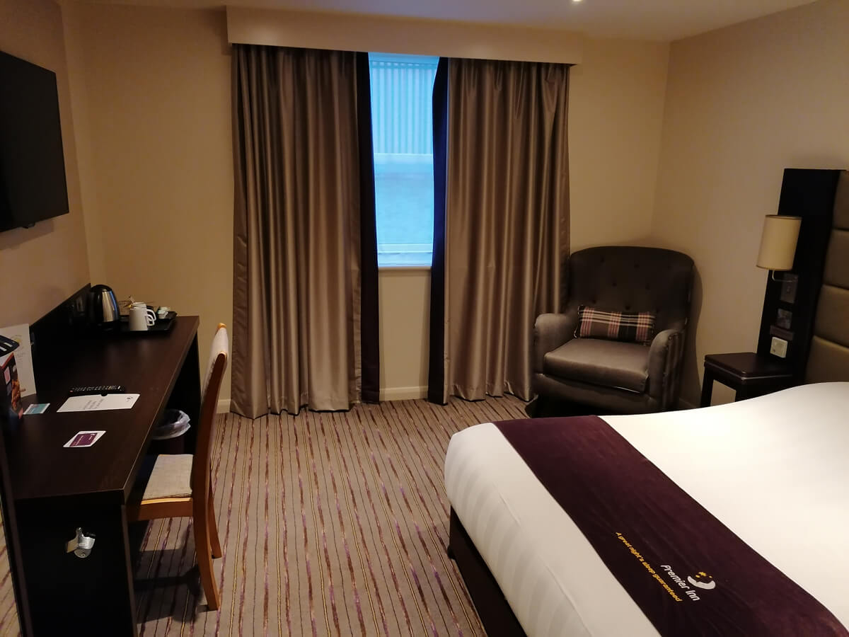 The double bed in the accessible room with the desk against the wall and an armchair in the corner of the room..