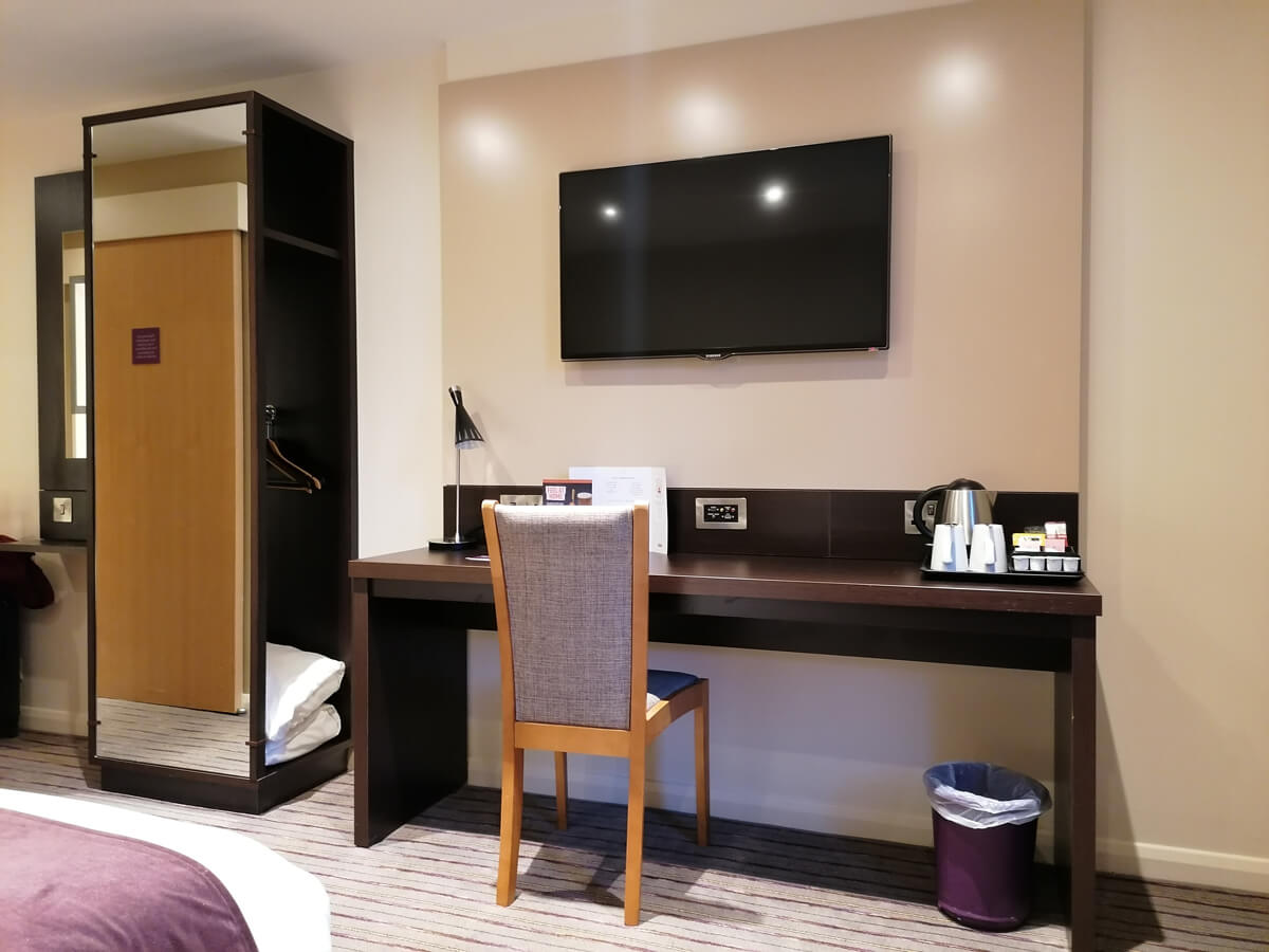 The work desk with a wall mounted TV above. The open wardrobe is also slightly in view.