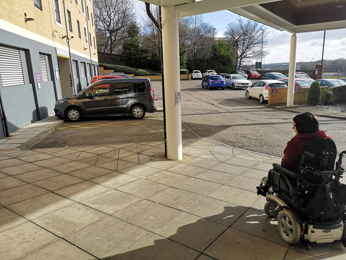 Emma driving towards her car parked in a disabled bay in the hotel car park.