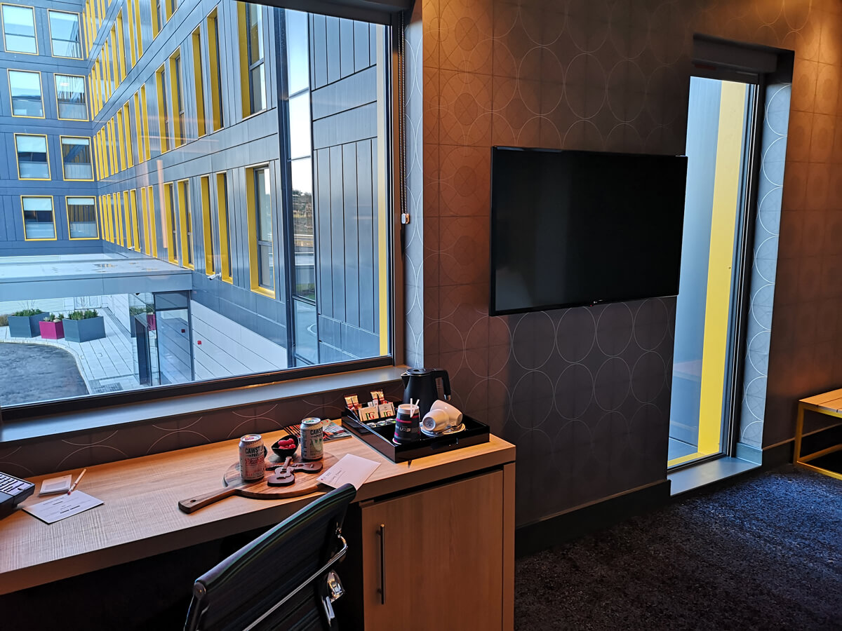A work desk positioned under the window. A TV is placed on the wall.