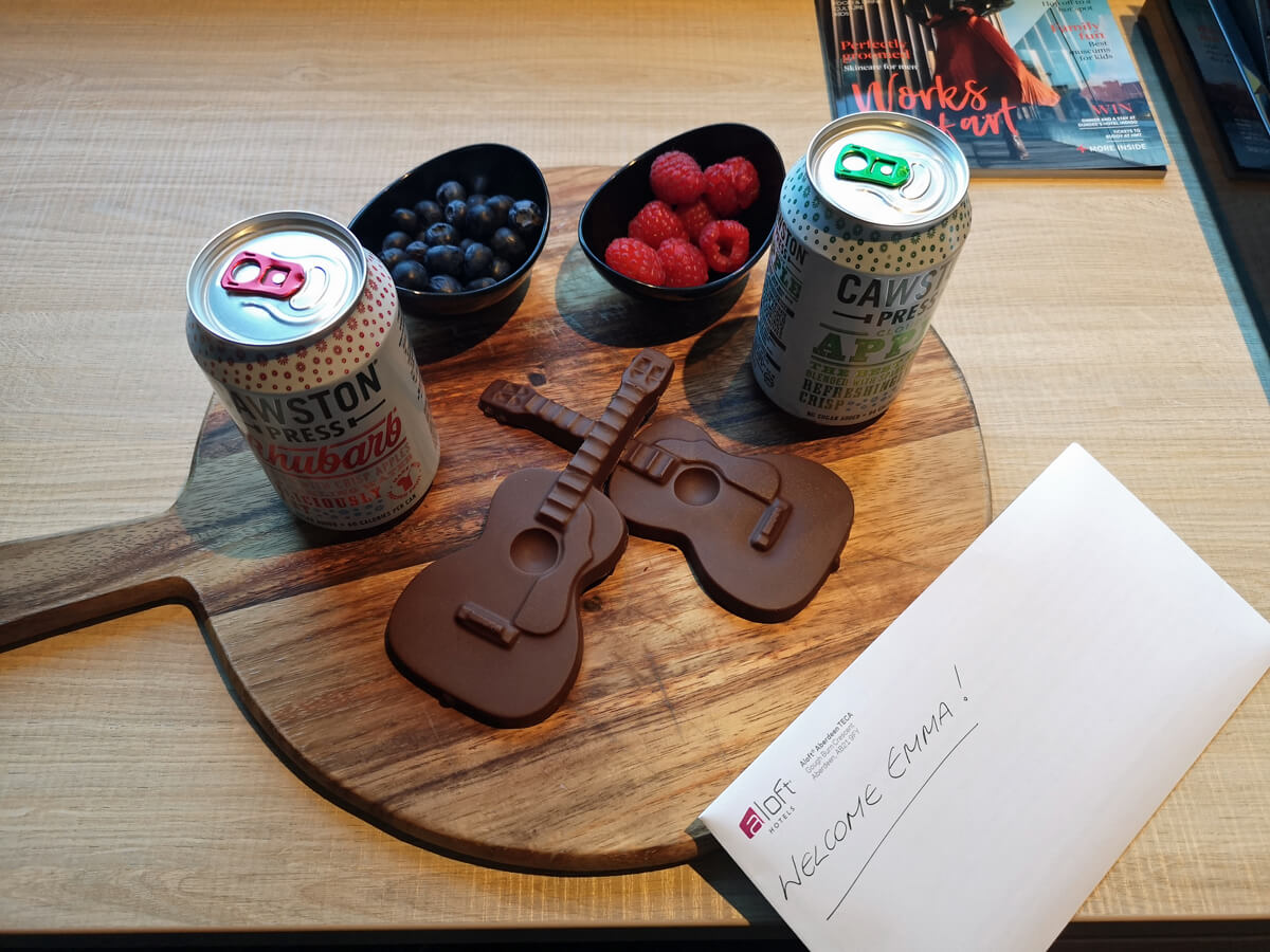 "Two chocolate shaped guitars, two cans of juice and two bowls of fruit with an envelop with ""Welcome Emma""."