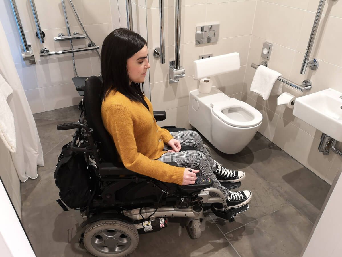 Emma sitting in her wheelchair in the accessible bathroom at Aloft Aberdeen TECA.