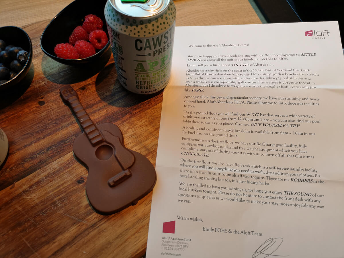 Two chocolate shaped guitars, two cans of juice and two bowls of fruit with a letter on the table.