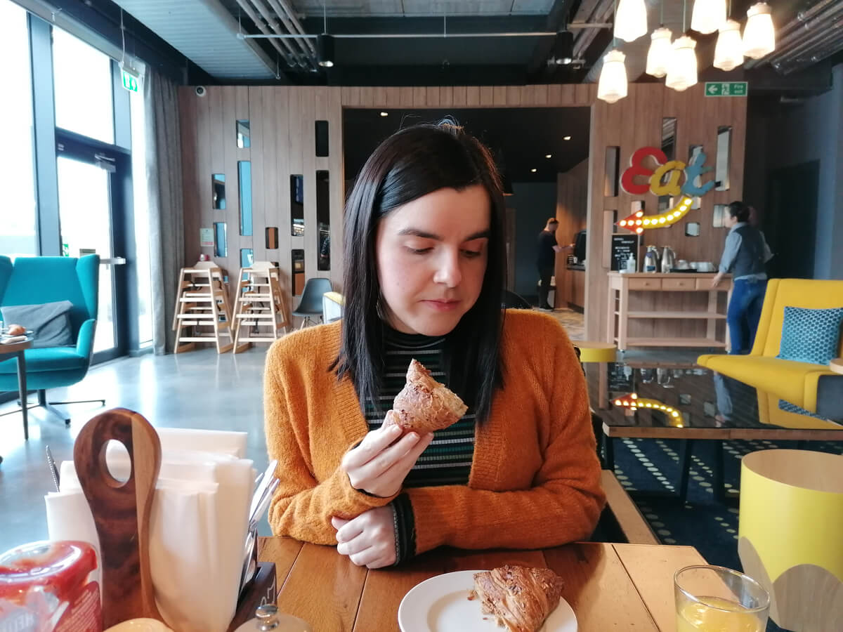 Emma eating a vegan croissant at Aloft Aberdeen TECA. She is wearing a mustard cardigan.