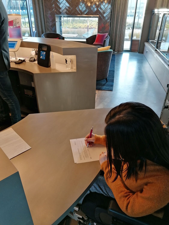 Emma filling in paperwork at the hotel reception desk.