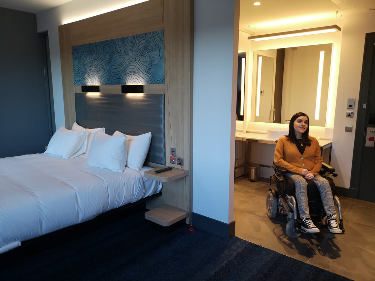 Emma sitting in her hotel room. She is sitting between the bathroom and bedroom.