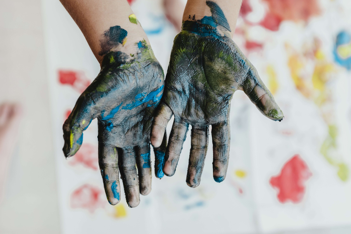 Kids hands covered in coloured paint.