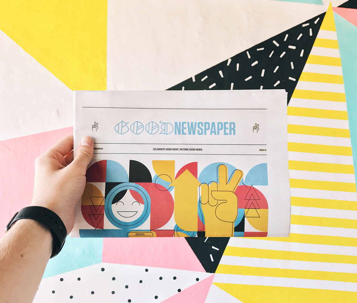A hand holding a colourful and vibrant newspaper called 'Good newspaper' against a colourful patterned wall.