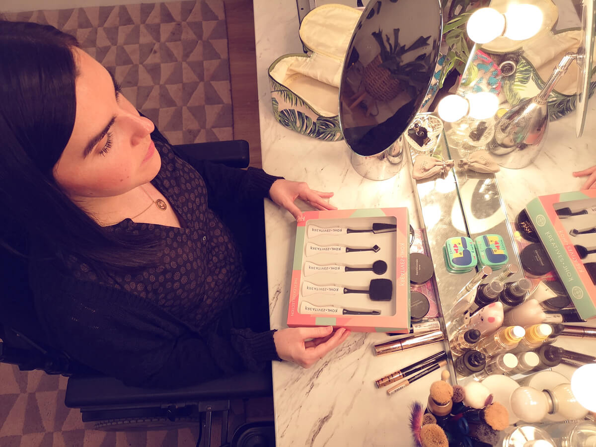 Emma sitting at her makeup vanity table surrounded by her makeup. Emma is holding a box displaying five makeup brushes.