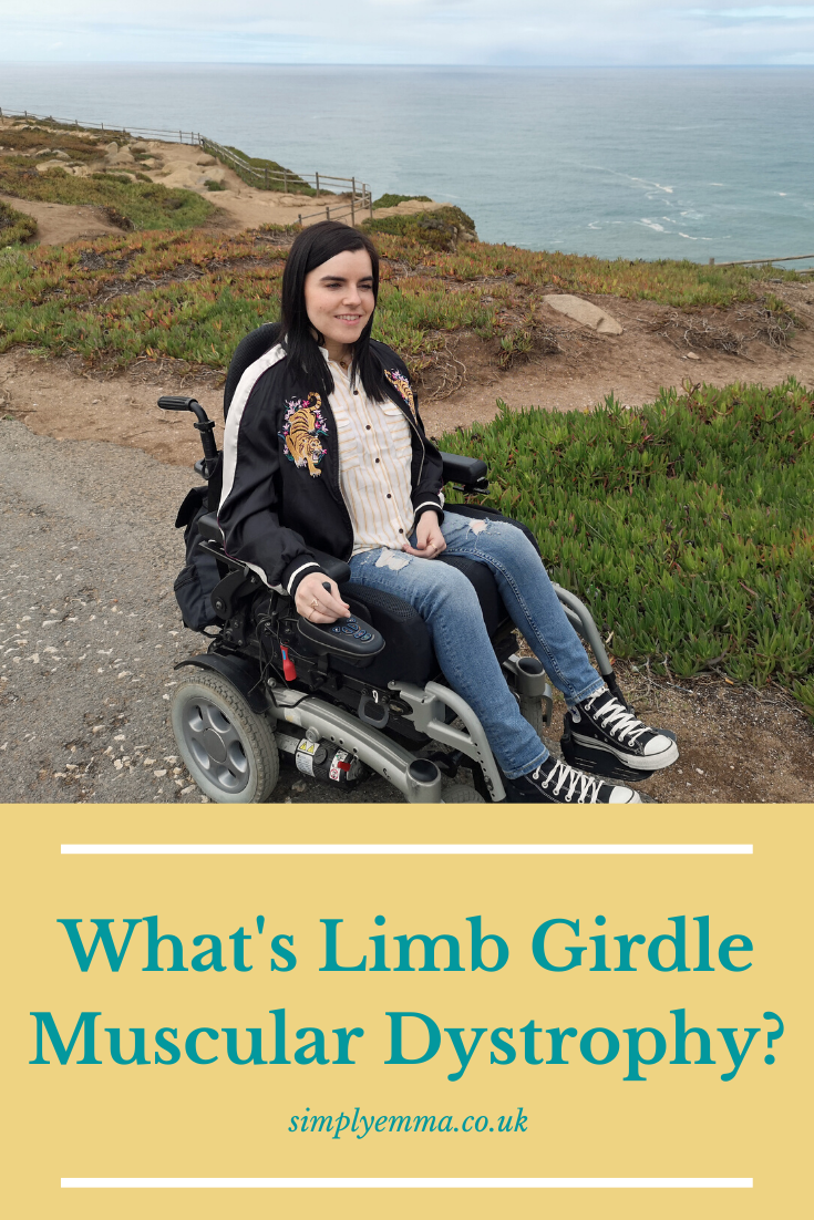 "Emma sitting in her powered wheelchair with the ocean behind her. The text below the image reads ""What's Limb Girdle Muscular Dystrophy. simplyemma.co.uk"""