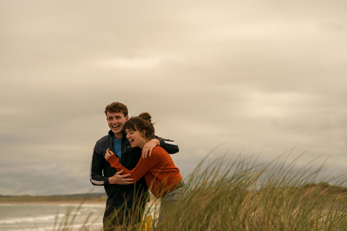 "Paul Mescal and Daisy Edgar-Jones as the central couple in ""Normal People,"" cuddling and smiling while walking along a beach."