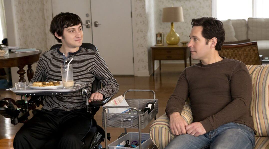 Trevor sitting in his wheelchair in his livingroom with Ben sitting next to him.