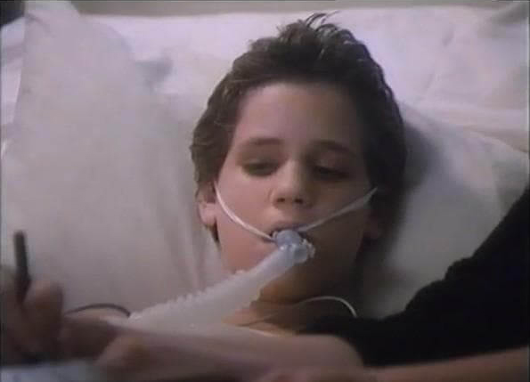 Corey Haim laying in a hospital bed in the movie A Life to Live.
