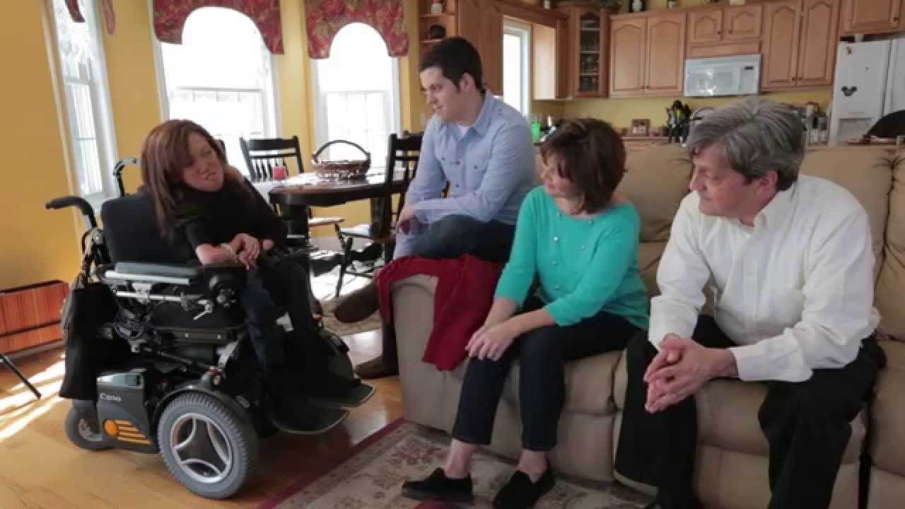Alyssa in her wheelchair sitting with her mum, dad and brother in the family livingroom.