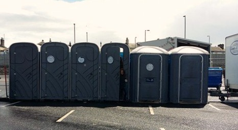 A row of portakabin toilets with two 'accessible' loos at the end.