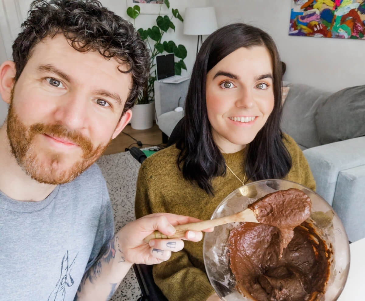 Emma and Allan smiling while holding a bowl of chocolate vegan batter. Allan is holding a wooden spoon.