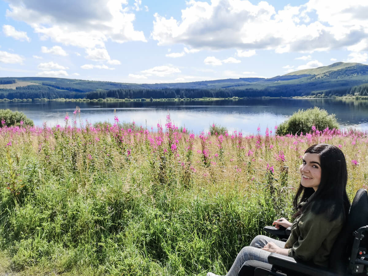 Emma sitting beside grass and purple flowers alongside the reservoir. The sky is blue with large white fluffy clouds. Emma is smiling.