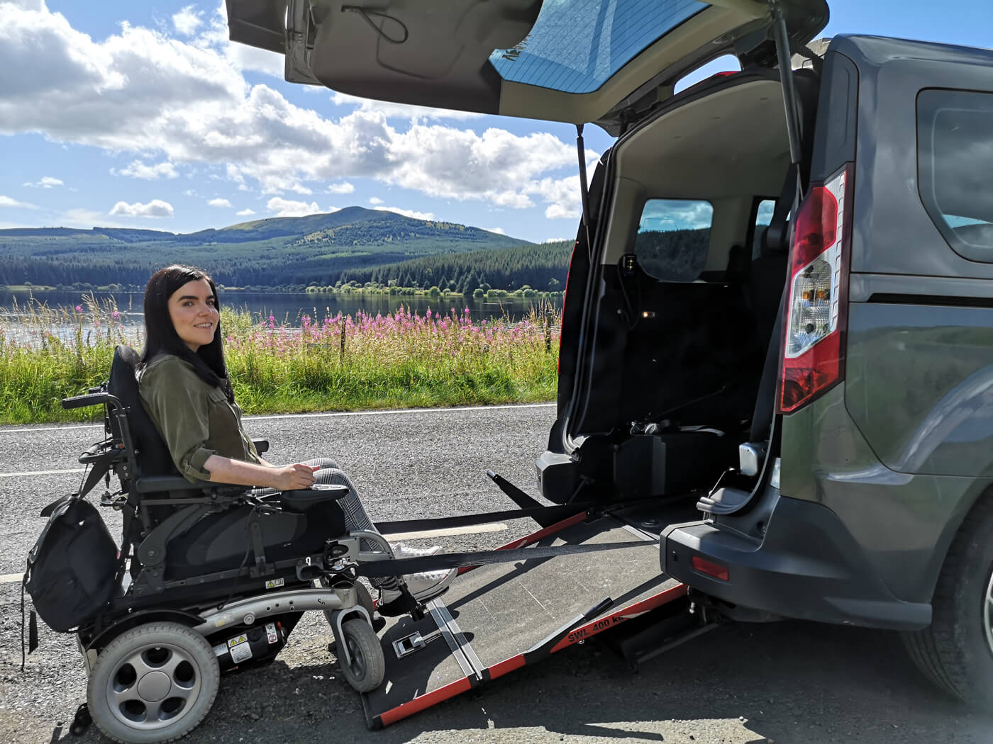 Emma sitting in her powered wheelchair at the bottom of the ramp of her wheelchair accessible vehicle. The Carron Valley Reservoir is behind her.