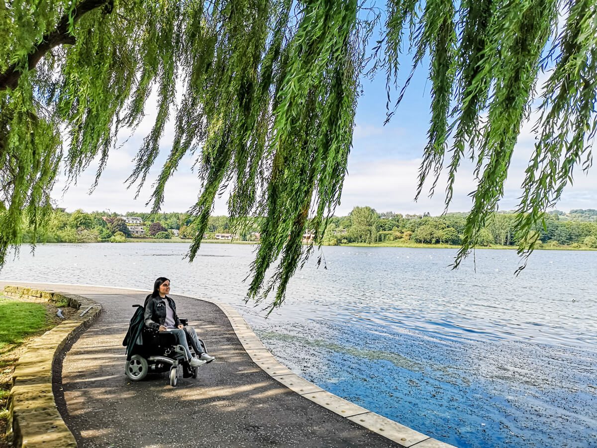 Emma in her powered wheelchair. She is sitting next to Linlithgow Loch under a willow tree. The sky is clear blue.