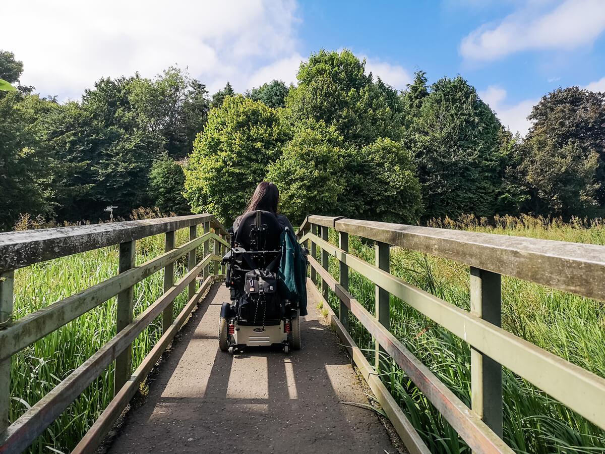 Emma driving her wheelchair across a wooden bridge.