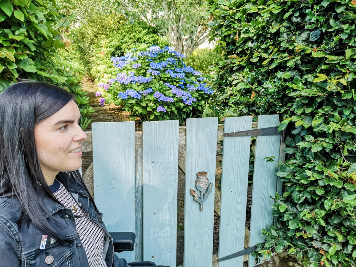 Emma sitting next to a pale blue wooden gate with a thistle emblem on it. There are lots of green trees and shrubs around her.