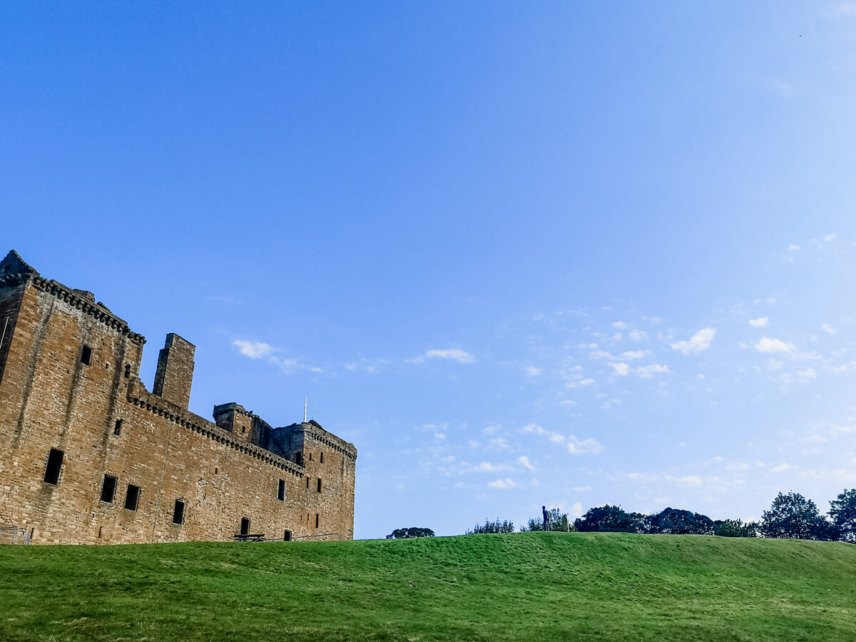 A close up shot of Linlithgow Palace. Vibrant green grass and clear blue sky frame the Palace.