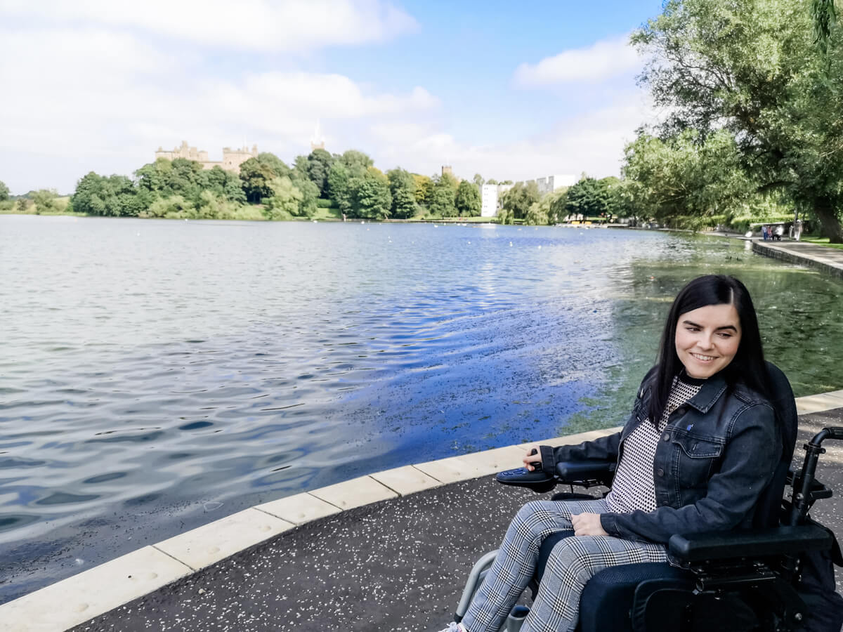 Emma in her powered wheelchair. She is sitting next to Linlithgow Loch under. Emma is looking down to the side and smiling.
