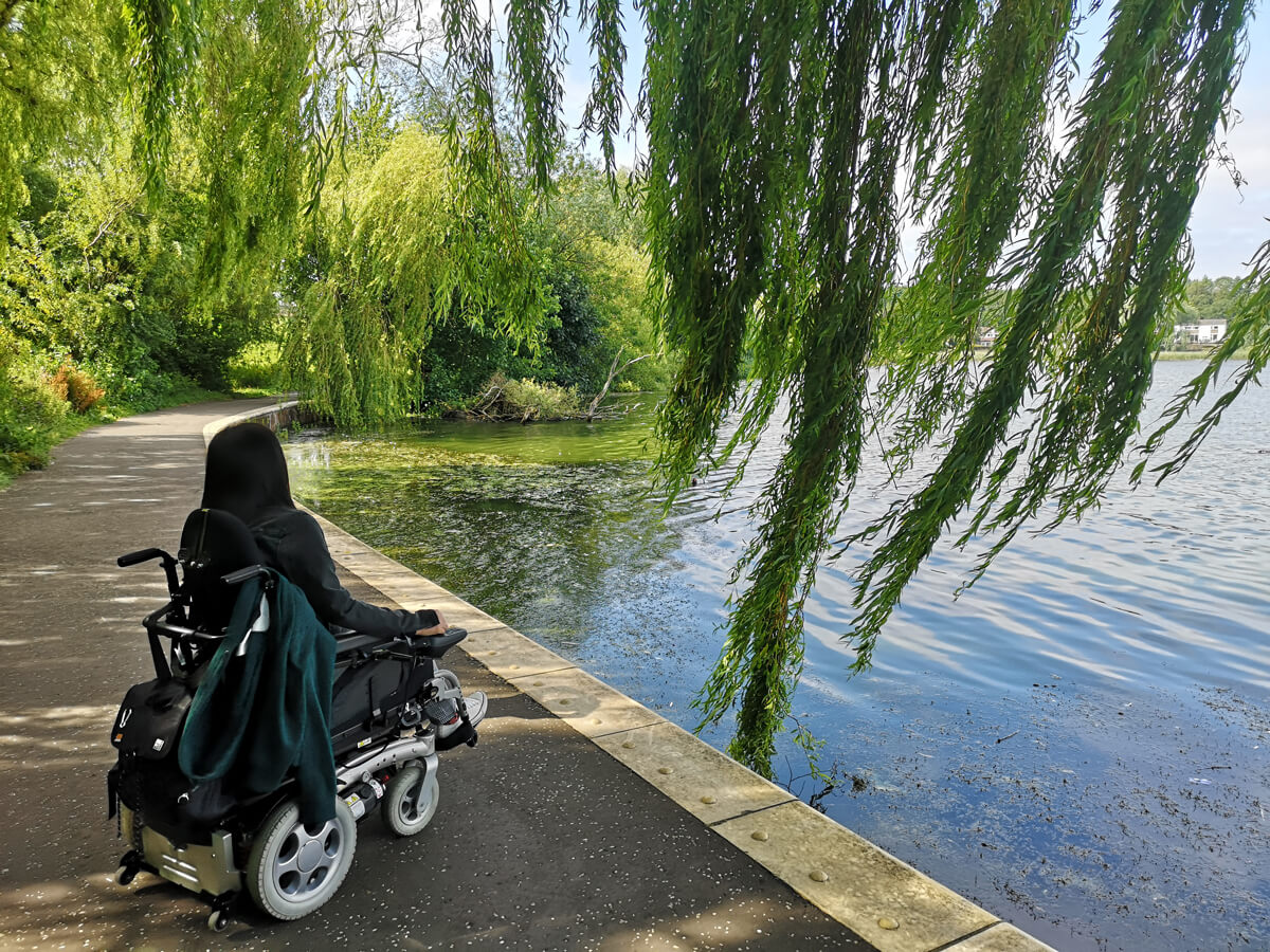 Emma sitting in her wheelchair with her back to the camera. She is sitting next the loch under a willow tree.