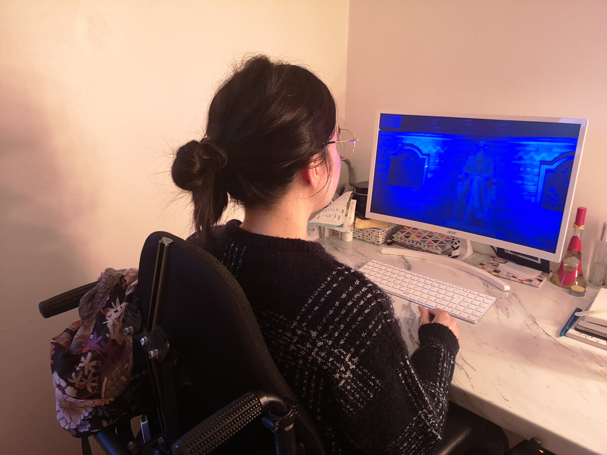 Emma sitting in her wheelchair with her back facing the camera. She is at her desktop PC watching Dermot Kennedy's virtual gig.