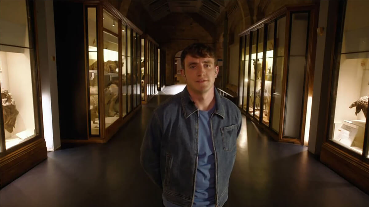 Paul Mescal standing in the Natural History Museum London hallway. He is looking straight into the camera.