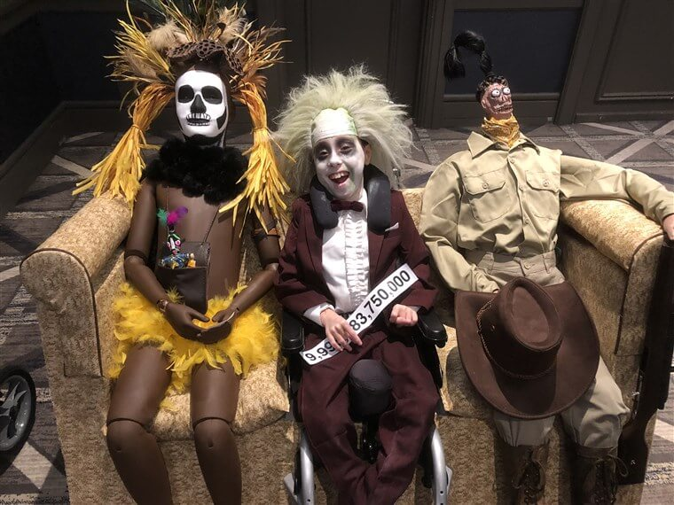 A young boy dressed as Beetlejuice creating a scene from the movie. He has transformed his wheelchair into the sofa with two characters from the movie for his wheelchair Halloween costume.