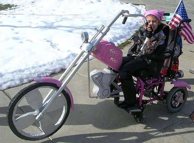 A young girl dressed as a biker wearing leathers and a pink head bandana. The girls wheelchair has been transformed into a bike harley davidson motorbike in this creative wheelchair halloween costume.