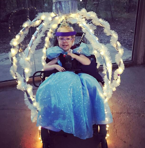 A young girl dressed as Cinderella. Her wheelchair has been transformed into a wheelchair accessible carriage for this wheelchair Halloween costume.