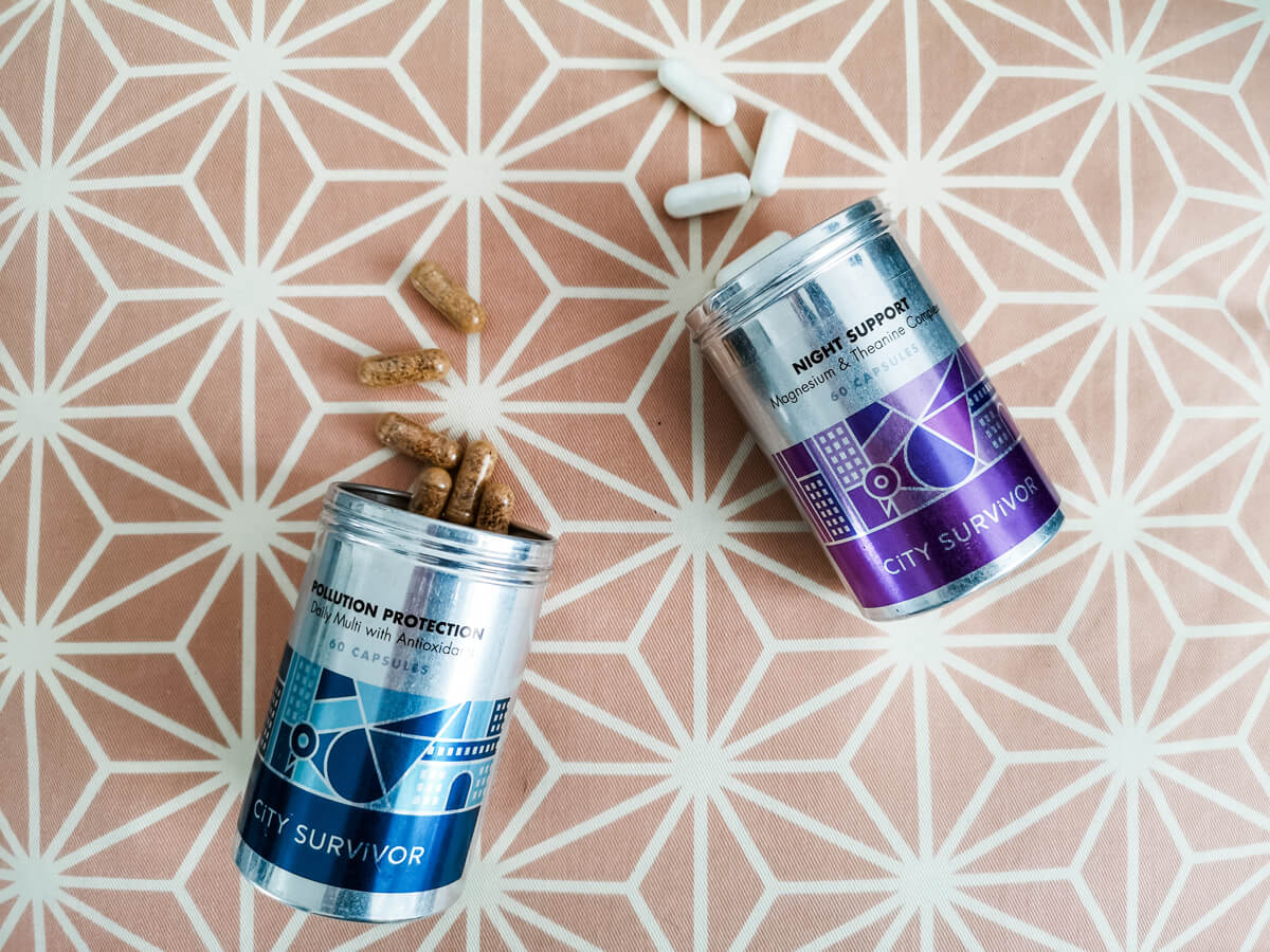 Two metal tins containing supplements. Pollution Protection has a blue design on the tin and Night Support has a purple design. The lids are off and the tins are laid on their sides with some of the supplement capsules scattered.