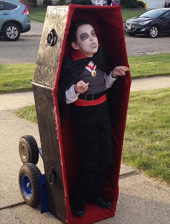 A young boy dressed as Dracula and standing inside a coffin for his wheelchair Halloween costume.