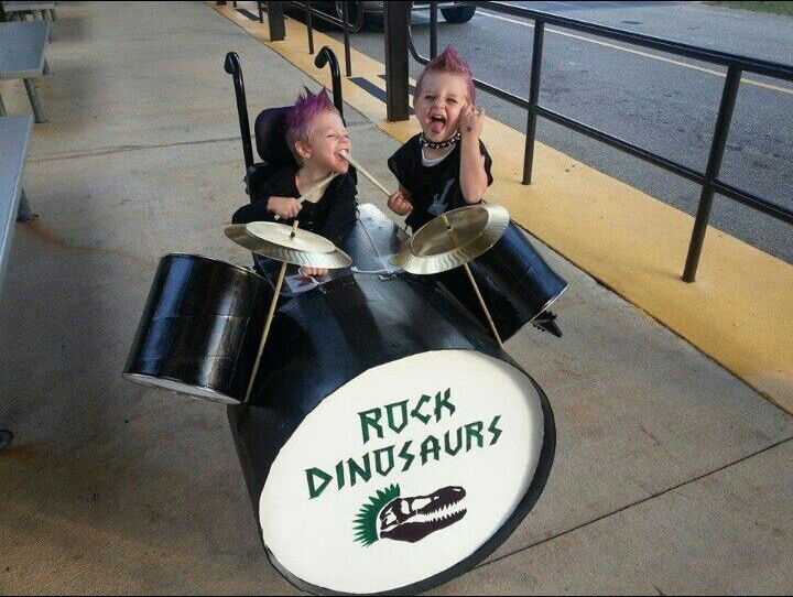A young boy dressed as a drummer of a band. His wheelchair has turned into a drum kit for his wheelchair Halloween costume.