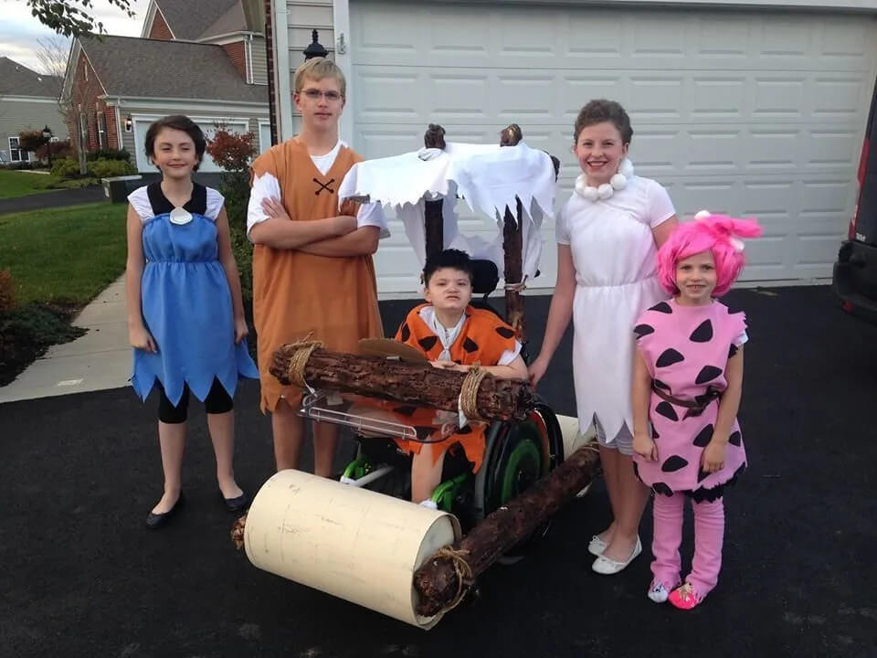 A young boy in a wheelchair dressed as Fred Flintstone. His family are all dressed up as the Flintstone family. The young boy has his wheelchair covered to look like the Flinstone vehicle.