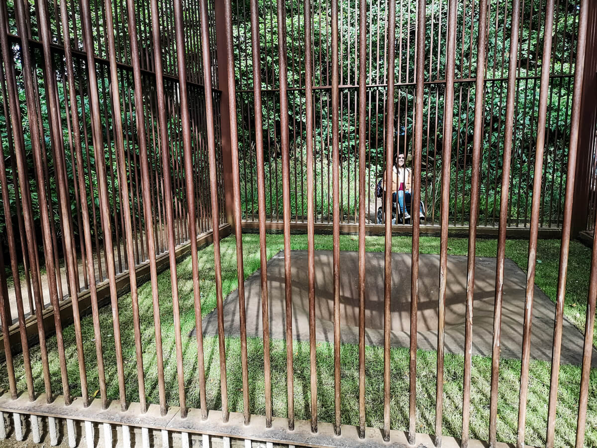 Emma in the distance between bars of the giant cage with a sink hole in the centre.