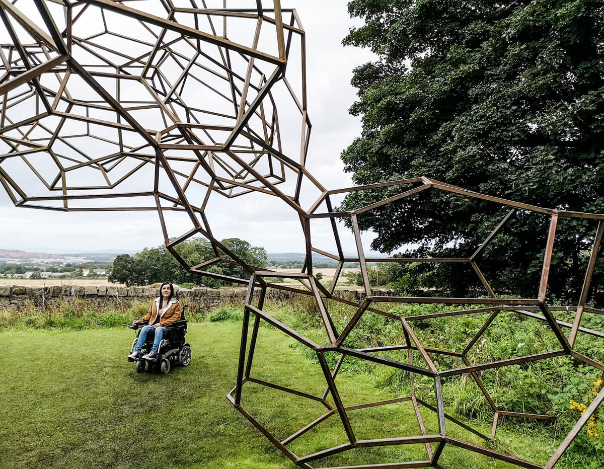 Emma sitting in her powered wheelchair on the grass under the Antony Gormley sculpture called 'Firmament'.